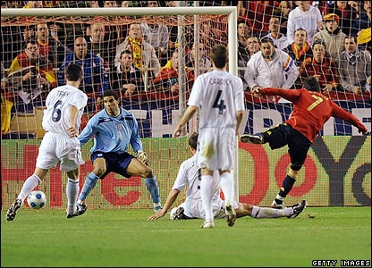 Spain's David Villa tucks the ball beyond David James