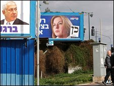An Israeli man walks beneath election posters for Tzipi Livni (R) and Benjamin Netanyahu in Tel Aviv, Israel, 11 February 2009