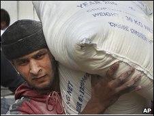 A Palestinian man carries a bag of flour at a United Nations distribution center in Gaza (20/11/2008)