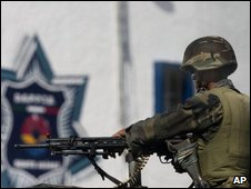 Soldier stand guard outside a police station in Cancun on 9 February 2009