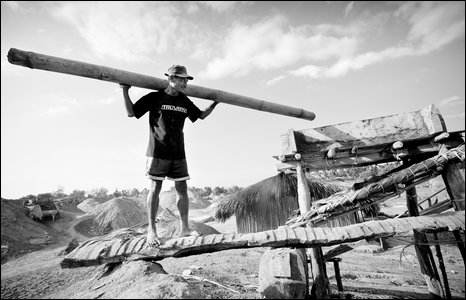 A salt worker uses a bamboo tube to pour sea water through a clay filter to make salt crystals.