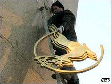 A worker removes the Sanlu logo from its headquarters