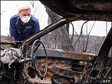A fire investigator examines the remains of a burnt out car in Victoria state