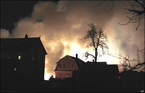 Homes silhouetted by smoke and flames