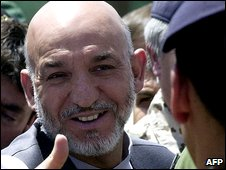 Afghan President Hamid Karzai shakes hands with soldiers of the International Security Assistance Force