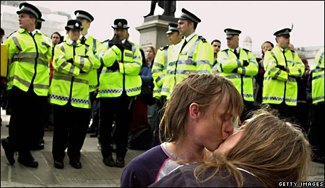 May Day protesters kiss by a row of police officers