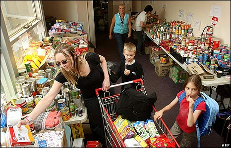 Karen Burton (L) and her eight-year-old twins collect food and clothing at a Whittlesea relief centre