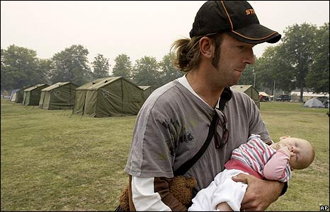 Sean Galpin carries his three-month-old daughter, Lucy, at a relief centre in Yea