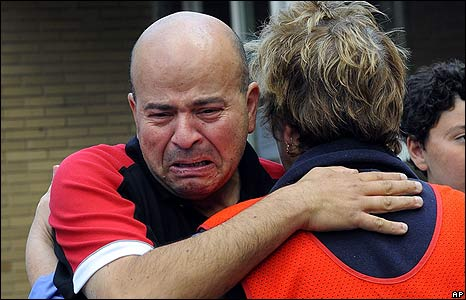 A survivor is consoled by a Country Fire Authority member outside the Healesville Relief Centre