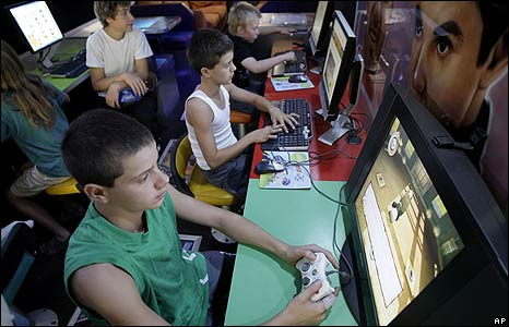 Tony Petkovski (L) and his brother Mark (C) play video games in a mobile youth centre bus at Yea