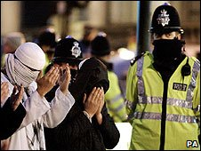 Muslims praying in front of policeman