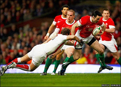 Stephen Jones attempts to evade the clutches of England's Andy Goode