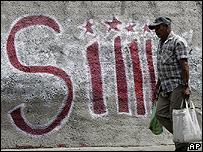 Un hombre camina frente a una pared que dice S�
