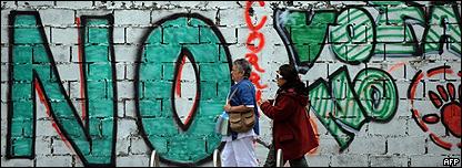 Dos mujeres caminan frente a una pared que dice No
