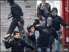 Youths throw rocks at an armoured police vehicle in Istanbul, Turkey, 15 February 2009