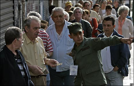 A soldier gives instructions to voters waiting outside a Caracas polling station