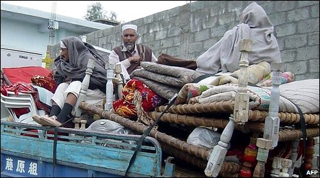 Pakistani residents sit on their belongings as they flee from the troubled Swat valley on February 3, 2009