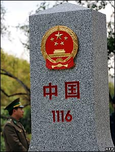 "A Vietnamese guard stands next to a marker for the ""Friendship Border Gate"" on the Chinese-Vietnamese border"