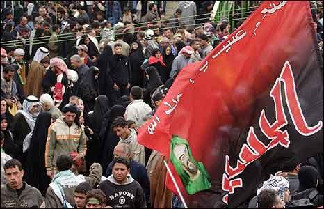 Crowds wave a Shia flag