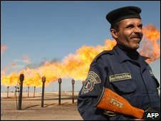 An officer guards a section of the Barjisiya oil fileds in Zubair One south west of the city of Basra