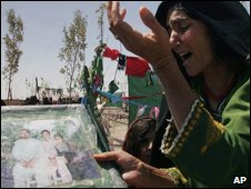 A distraught Afghan woman holds images of her family members killed in August 2008 during a US led raid