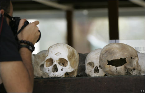 Tourist taking picture of skulls at Choeung Ek