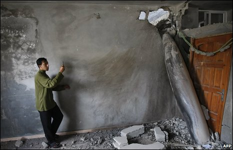 A Palestinian youth takes a picture with a mobile phone of an unexploded projectile in a house following an Israeli air strike in Gaza City on January 3, 2009