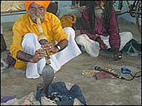 Un hombre encanta a una cobra negra (Foto de archivo)