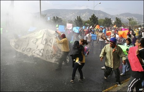 Protesters run for cover as police use a water cannon in Monterrey, Mexico, 17 February 2009