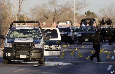 A police officer walks near a bullet-riddled police vehicle in Ciudad Juarez, Mexico, 17 February 2009