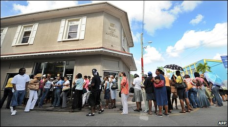 Customers queue outside a Bank of Antigua branch in St John's