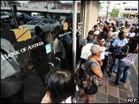 Personas hacen fila frente al banco de Antigua.
