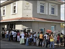 People queue outside the Bank of Antigua following owner Sir Allen Stanford being charged with fraud