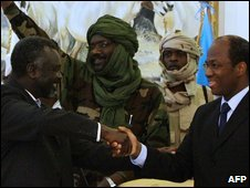 Jem leader Khalil Ibrahim (back, centre) waves as his brother Dr Jibril Ibrahim shakes hands with UN/AU mediator Djibril Bassole (R) on 17 February 2009