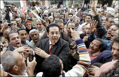 Freed Egyptian dissident Ayman Nour, center, seen surrounded by his supporters as he arrives at his party's headquarters in Cairo