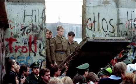 East German border guards look through a hole in the Berlin Wall