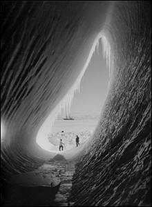 Team members examine a crevice in the ice with the Terra Nova in the background, 5 January 1911.