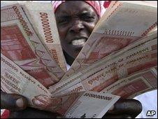 A woman holding Zimbabwean dollar notes