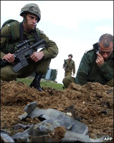 Israeli soldiers examine the remains of a rocket fired from Lebanon and landed near a private residence in the western Galilee, near the northern Israeli town of Maalot