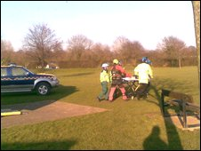 Coastguard and ambulance crews transporting injured man