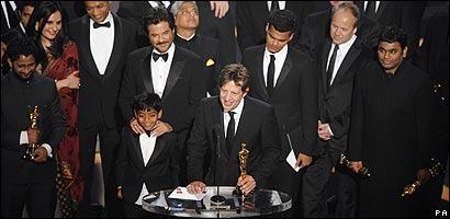 El productor de Slumdog Millionaire sostiene la estatuilla rodeado por el elenco