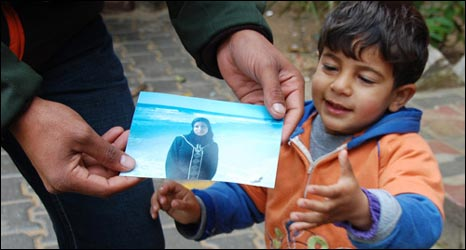 Muhammad Abu Jarad holding a photo of his dead wife, with Khalil, aged 2