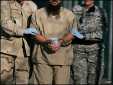 Detainee being escorted by camp guards in 2006