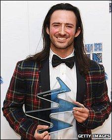 Aaron holds his Breakthrough Award trophy