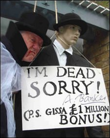 An activist with a banker effigy
