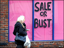 A woman walks past a shop window in Wigan, north-west England
