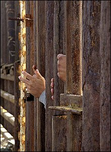 Immigrants hands reach through the fence