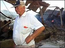 File pic of a farm owner walking through the shell of his tobacco barn, torched by war veterans, near Harare