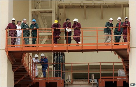 Russian and Iranian engineers watch visitors to Bushehr plant
