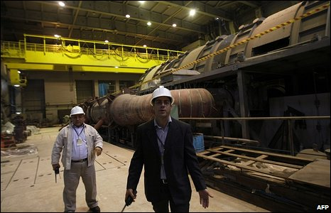 Iranian officials from the Atomic Energy Organization ask photojournalists to leave the turbine building during an organised tour in the Bushehr nuclear power plant